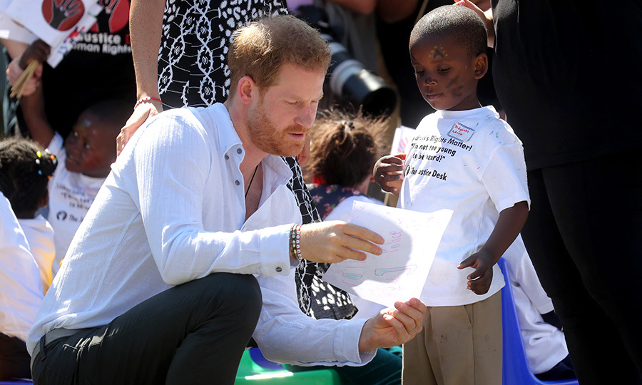 "The little boy was keen to show Harry his drawing. He was also wearing a shirt that reads, ""Children's rights matter! I'm not too young to be heard!""