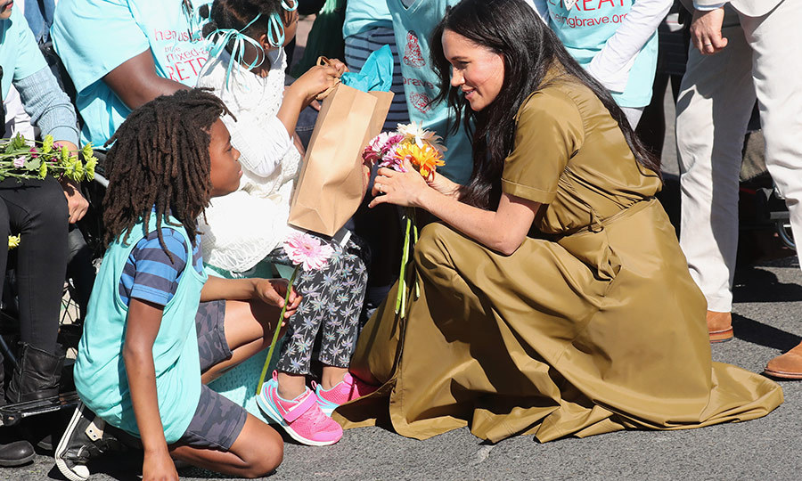 After leaving the mosque, Meghan and Harry said hello to wellwishers at a Heritage Day celebration, including this youngster. Heritage Day recognizes South Africa's many cultures and religious groups. Modern South Africa is known as the Rainbow Nation, and its new flag, adopted in 1994, reflects this.