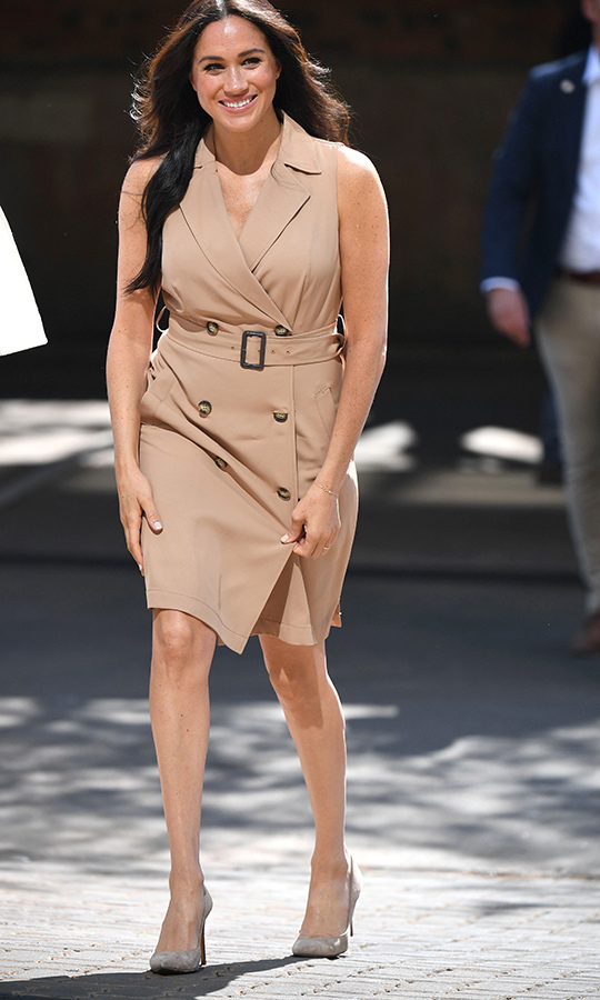"For her first event on Oct. 1, Meghan stepped out to the University of Johannesburg in a stunning camel double-breasted trenchcoat dress from <strong><a href=""/tags/0/banana-republic"">Banana Republic</a></strong> and nude heels from <strong><a href=""/tags/0/stuart-weitzman"">Stuart Weitzman</a></strong>.