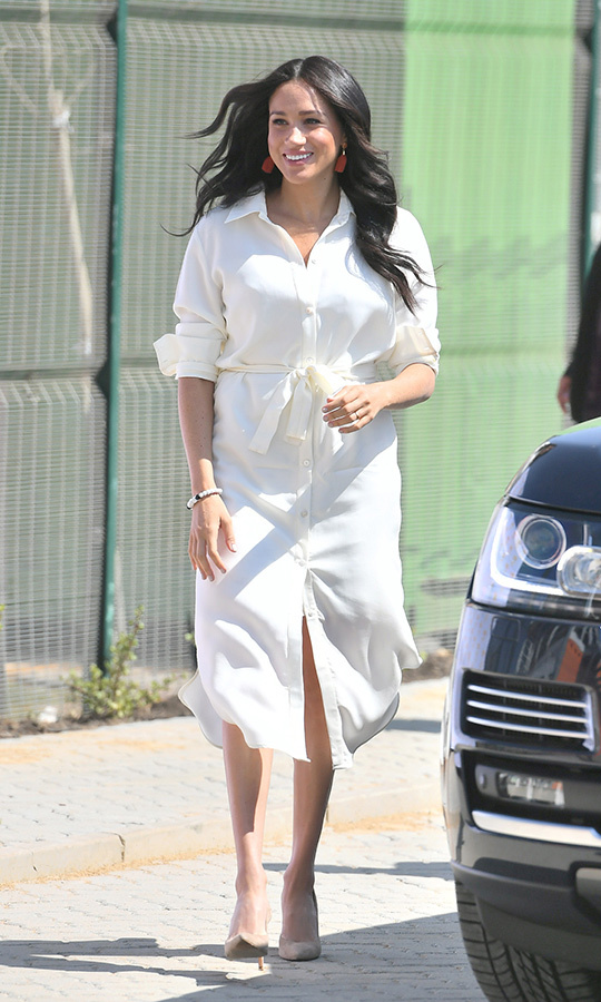 On Oct. 2, Meghan stepped out for her morning engagement with Harry in a white shirt dress by Cape Town sustainable fashion designer <strong>Hannah Lavery</strong>. She paired it with nude heels and a pair of red statement tassel earrings and looked FABULOUS.