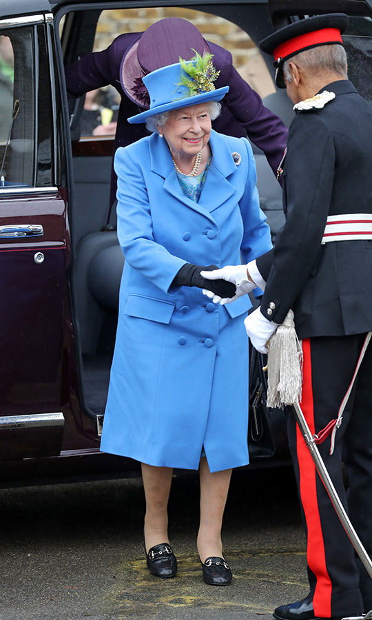 Her Majesty sported a beautiful cornflower blue coat by <strong>Angela Kelly</strong>, which she paired with a matching hat decorated with a lovely green feather adornment. On her feet were her favourite flats, and she appeared to be wearing the Russian Sapphire Cluster brooch!