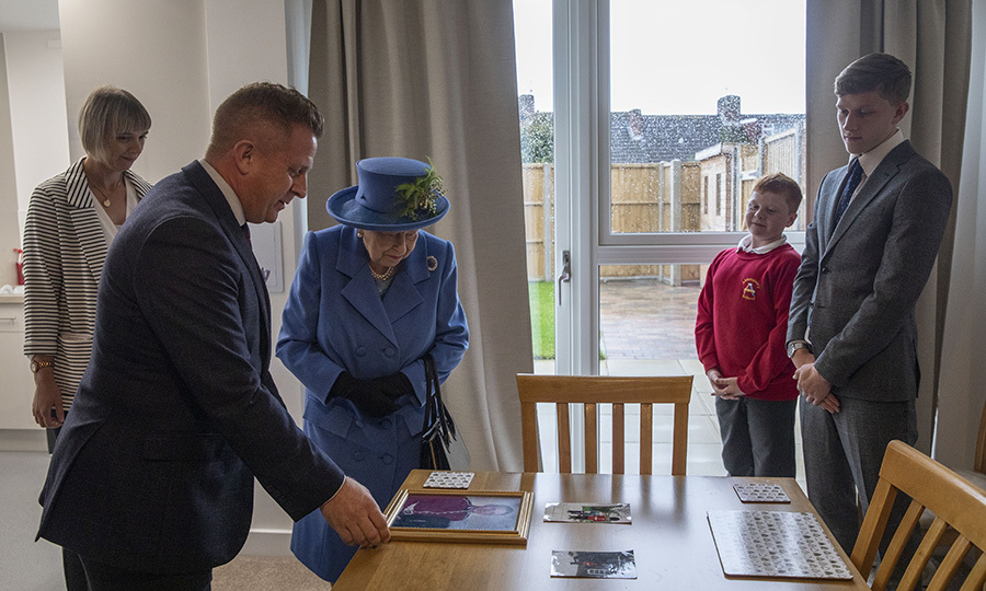While inside, Her Majesty visited with the Bowman family, who have been living in the housing block for a while and wanted to show her some of their photos. 