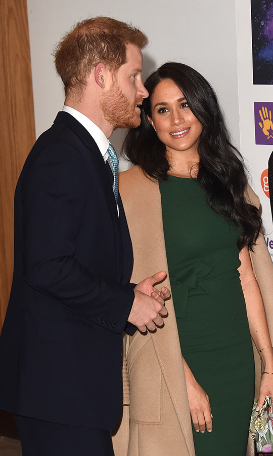 Meghan looked lovingly at her husband as he spoke to them about their work.