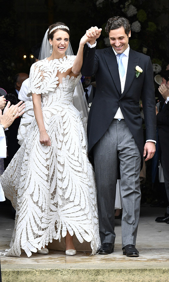 The bride and groom emerged from the chapel holding hands in a double fistpump of sorts after they were wed.