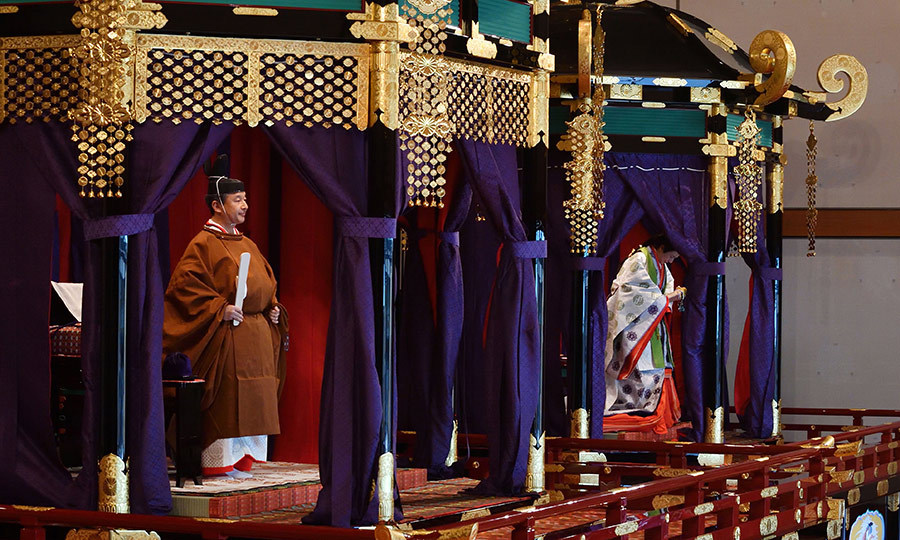 Once the ceremony began, a curtain was pulled back on a giant stage, revealing Naruhito and Masako, seated in regal robes.