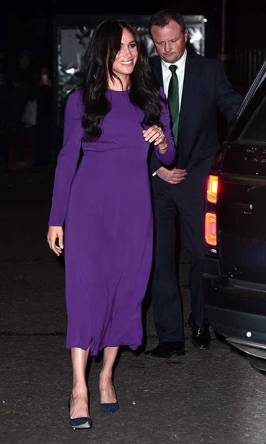 "Meghan re-wore a purple <strong><a href=""/tags/0/aritzia"">Aritzia</a></strong> midi dress for the occasion, which she paired with blue heels. She kept her hair down and wore it in loose waves. 