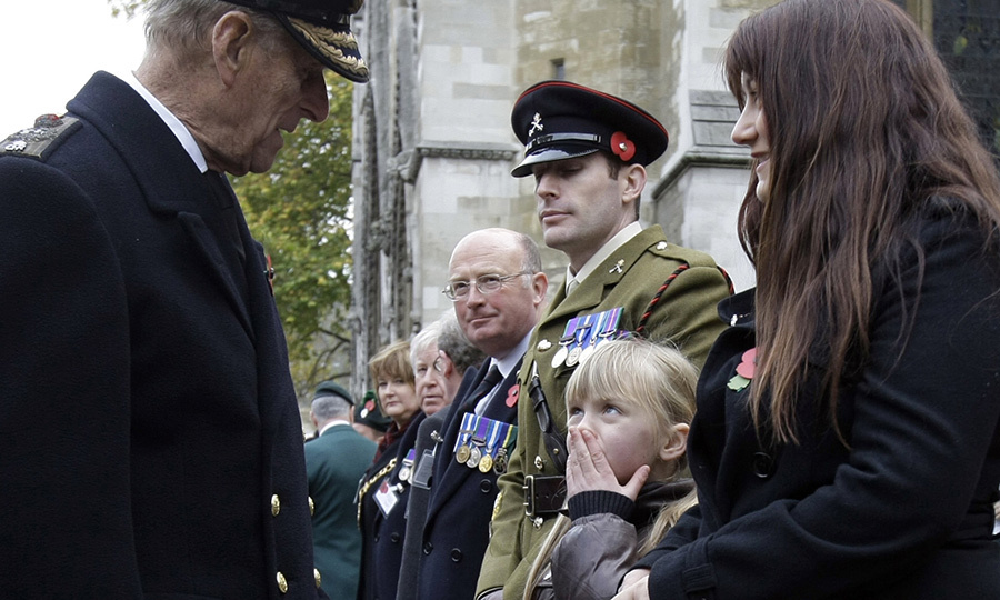 <strong>Paygan Russell</strong>, daughter of <strong>Russell Aston</strong>, a British military police officer killed in Iraq in 2003, looks up at Prince Philip as he tours the Garden of Remembrance outside Westminster Abbey in November 2009.