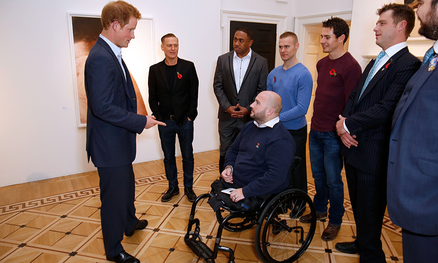"Prince Harry speaks with photographer <strong>Bryan Adams</strong> and servicemen at the private view of ""Wounded: The Legacy of War"" at Somerset House on Remembrance Day 2014.