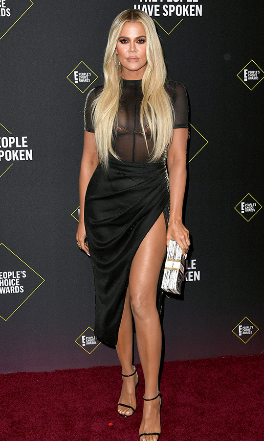 "<strong><a href=""/tags/0/khloe-kardashian"">Khloe Kardashian</a></strong> chose a sheer black dress and accessorized with a clutch that looked like a massive stack of money.