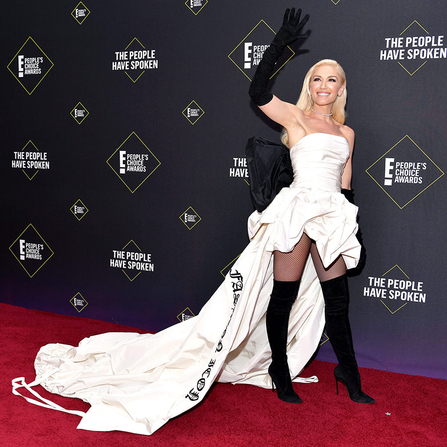 "Fashion icon delivers! <strong><a href=""/tags/0/gwen-stefani"">Gwen Stefani</a></strong> was named Fashion Icon of the Year the People's Choice Awards and definitely dressed the part! She chose a gorgeous white gown with a huge train that appropriate had ""FASHION ICON"" emblazoned on it, which she paired with knee-high suede boots and black gloves. 