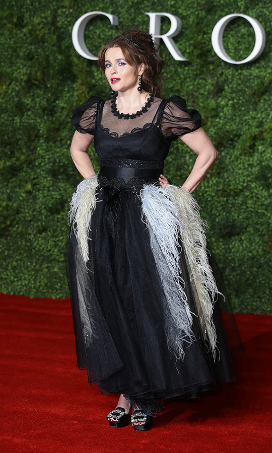 "<strong><a href=""/tags/0/helena-bonham-carter"">Helena Bonham Carter</a></strong>, who plays <strong><a href=""/tags/0/princess-margaret"">Princess Margaret</strong></a>, showed off some of her very unique style on the red carpet, wearing a black sheer and lace dress with red accents that resembled feathers. She paired it with chunky black heels with silver accents and accessorized with black earrings. 