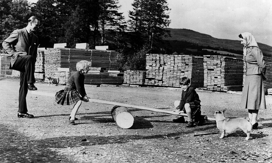 As Charles and Anne continued to grow, the family valued their time at Balmoral became even more important during the summer months. Here, Anne and Charles make an improvised see-saw in 1957. 