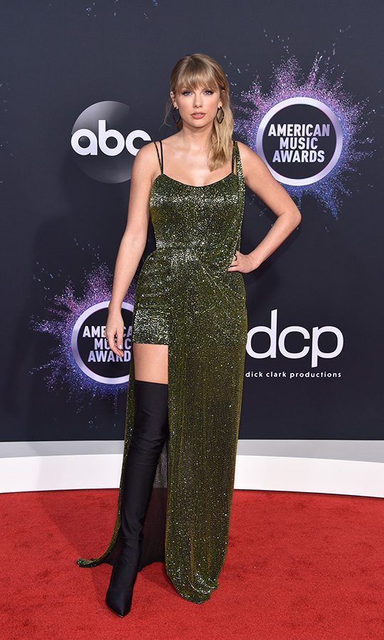 "<strong><a href=""/tags/0/taylor-swift"">Taylor Swift</a></strong> was the queen of asymmetrical looks, rocking a shimmering green gown that showed off her right leg and the incredible knee-length boots she was wearing!
