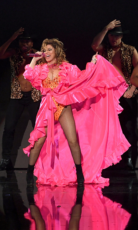 "But then the performance went up a few notches – like, a lot, in a way that will (pardon us) impress you much. Shania stood up, and revealed her pink dress actually had an orange sequinned bodice underneath it, to which she'd added fishnet tights. The ""pink dress"" was actually a cape! 