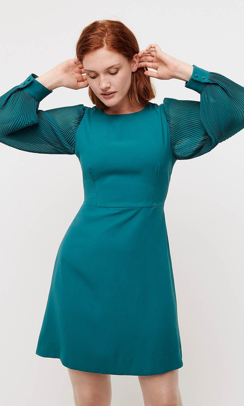 <p>The fun pick has added interest from the long pleated sleeves. It also features a fitted waist and skirt that falls to the knee. There's no need to worry about altering it because it is available in classic, petite and tall fits.