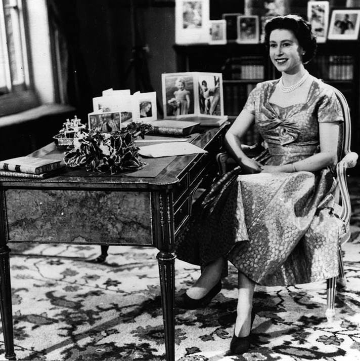 "<h2>1957</h2></p><p>This heart-warming photo of Her Majesty's very first televised Christmas speech captures her smiling at <a href=""https://ca.hellomagazine.com/tags/0/prince-philip"" target=""_blank""><strong>Prince Philip</strong></a> at the end of the broadcast! Royal fans were treated to a good look at her printed dress with knotted bodice, albeit the recording was in black and white!</p><p>Photo: © Keystone/Getty Images"