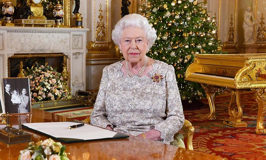 "<h2>2018</h2></p><p>What a marvellous image! This photo of the Queen after she recorded her annual Christmas Day message in the White Drawing Room at Buckingham Palace has festive spirit! The glistening lace fabric and pointed neckline of her dress have such impact. The Queen accessorized with the gold, ruby and diamond ""Scarab"" brooch Prince Philip gave to her in 1966. It has also been featured in a few other Christmas speech ensembles!</p><p>Photo: © John Stillwell - WPA Pool/Getty Images"