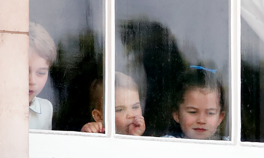 Earlier in the day, all three of the Cambridge kids were spotted peeking out one of Buckingham Palace's windows at the crowds.