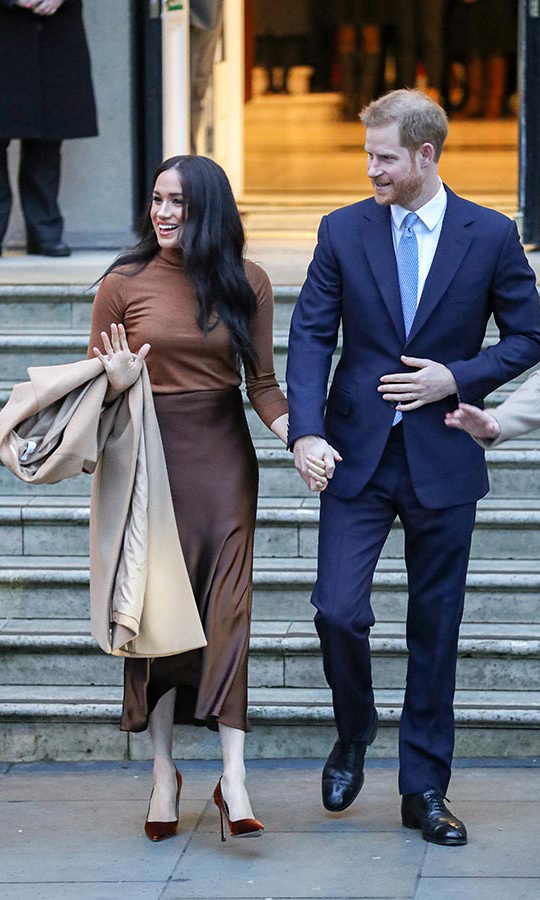 Meghan took her coat off while she was inside, giving us a better look at her gorgeous outfit when she and Harry left.