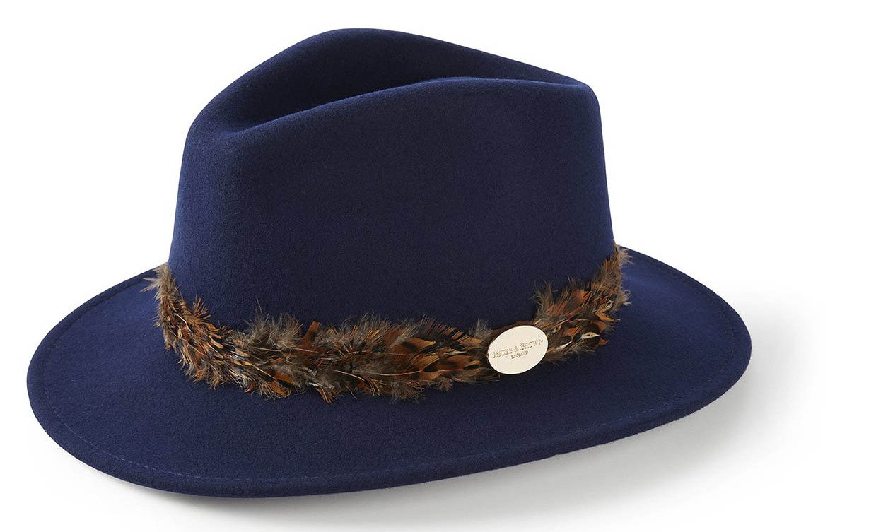 "This is reportedly the striking hat that Duchess Kate wore! The wool felt Suffolk Fedora by <strong>Hicks & Brown</strong> is hand-finished with a pheasant feather wrap. It is available in sizes extra-small to large.</p><p>The Suffolk Fedora in Navy (Pheasant Feather Wrap), $162.19, <a href=""https://www.hicksandbrown.com/collections/the-suffolk-fedora-navy/products/the-suffolk-fedora-with-pheasant-feather-wrap-2?variant=3882887905320"" target=""_blank"">Hicks & Brown</a></p><p>Screenshot via hicksandbrown.com"