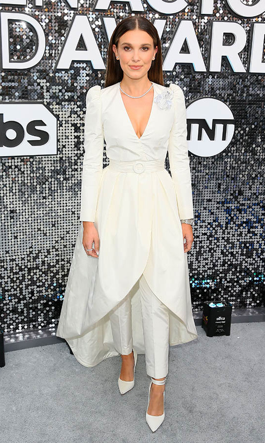 <i><strong><a href=/tags/0/stranger-things>Stranger Things</a></strong></i>' <a href=/tags/0/millie-bobby-brown><strong>Millie Bobby Brown</a></strong> donned a chic white look featuring a dress <i>and</i> pants. <p>Photo: &copy; JEAN-BAPTISTE LACROIX/AFP via Getty Images