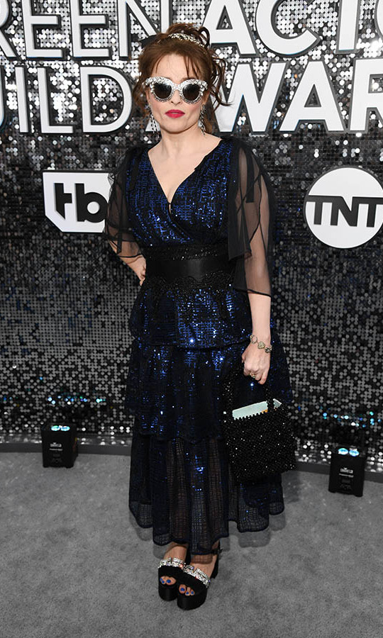 <a href=/tags/0/the-crown><strong><i>The Crown</a></strong></i>'s <a href=/tags/0/helena-bonham-carter><strong>Helena Bonham Carter</strong></a> looked cool in glittering sunglasses, hair accessories and a sequinned dress! <p> Photo: &copy; Kevin Mazur/Getty Images for Turner