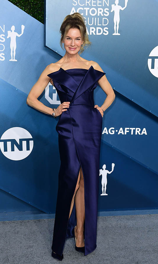 <a href=/tags/0/renee-zellweger><strong>Renée Zellweger</strong></a> smiled bright in a deep purple strapless gown. <p>Photo: &copy; FREDERIC J. BROWN/AFP via Getty Images