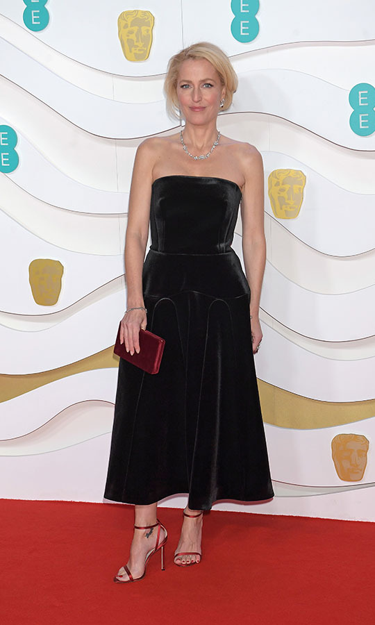 <a href=/tags/0/gillian-anderson><strong>Gillian Anderson</strong></a> looked timeless in a strapless black dress with deep red accessories. <p>Photo: &copy; David M. Benett/Dave Benett/Getty Images