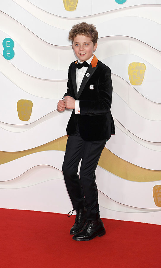 <em>Jojo Rabbit</em> actor <strong>Roman Griffin Davis</strong> had a blast on the BAFTAs red carpet in a cool black suit with contrasting orange collar. <p>Photo: &copy; David M. Benett/Dave Benett/Getty Images
