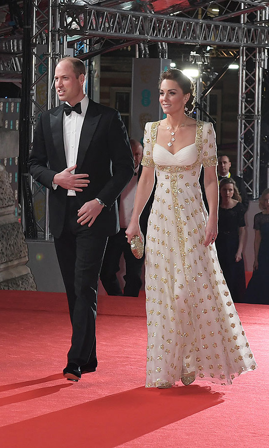 What an entrance! <a href=/tags/0/prince-william><strong>Prince William</strong></a> and <a href=/tags/0/kate-middleton><strong>Duchess Kate</strong></a> looked incredibly chic as they stepped onto the BAFTAs red carpet. She followed the awards ceremony's suggestion of dressing sustainably by rewearing a white and gold <a href=/tags/0/alexander-mcqueen><strong>Alexander McQueen</strong></a> gown she wore on the couple's 2012 tour of Malaysia. The duchess paired the sparkling gown with <a href=/tags/0/jimmy-choo><strong>Jimmy Choo</strong></a> pumps. <p>Photo: &copy; David M. Benett/Dave Benett/Getty Images