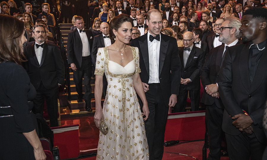 Once they were inside, everyone stood as the Cambridges arrived. 