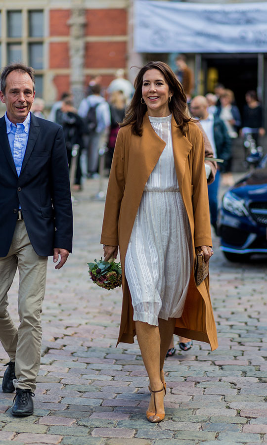Crown Princess Mary stepped out in style to the Copenhagen Fashion Week Spring/Summer 2017 shows in Aug. 2016 in a white dress and toffee-coloured coat. <p>Photo: &copy; Christian Vierig/Getty Images