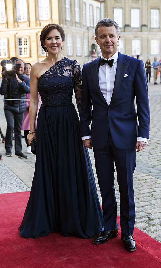 Outfitted in a navy gown with asymmetrical lace sleeve, Mary defined elegance alongside Crown Prince Frederik at <strong>Princess Benedikte</strong>'s 75th birthday party at Amalienborg Palace on April 29, 2019 in Copenhagen. <p>Photo: &copy; Ole Jensen/Getty Images