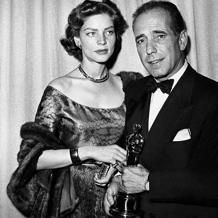 <strong>Humphrey Bogart</strong> and then-wife <strong>Lauren Bacall</strong> posed at the 1952 Academy Awards with his Oscar for Best Actor. He won for his role in <em>The African Queen</em>. <p>Photo: &copy; Frank Worth, Courtesy of Capital Art/Getty Images