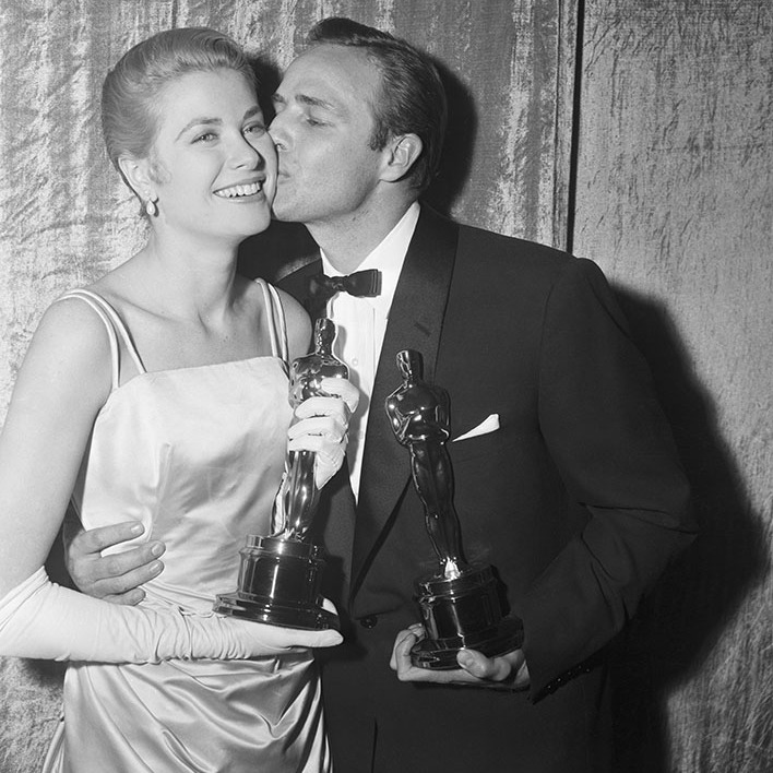 At the 1955 Academy Awards, Oscar winner <strong>Grace Kelly</strong> gets a kiss from fellow winner <strong>Marlon Brando</strong>. They won best acting awards in their categories for <em>The Country Girl</em> and <em>On the Waterfront</em>, respectively. <p>Photo: &copy; Bob Grosh and Dave Cicero