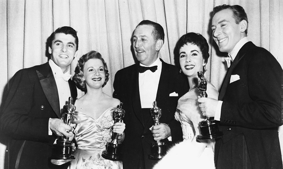 <strong>Walt Disney</strong> (centre) celebrates his record-breaking four Oscars at the 1954 Academy Awards with presenters <strong>Elizabeth Taylor</strong> (second right) and <strong>Michael Wilding</strong> (right).<p>Photo: &copy; Archive Photos/Getty Images