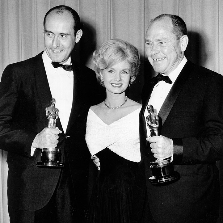 "At the 1963 Oscars, presenter <a href=/tags/0/debbie-reynolds><strong>Debbie Reynolds</strong></a> posed with composer <strong>Henry Mancini</strong> (left) and lyricist <strong>Johnny Mercer</strong> (right), winners of the Academy Award for Best Song for ""Days Of Wine And Roses"" from the film of the same name. <p>Photo: &copy; Michael Ochs Archives/Getty Images"