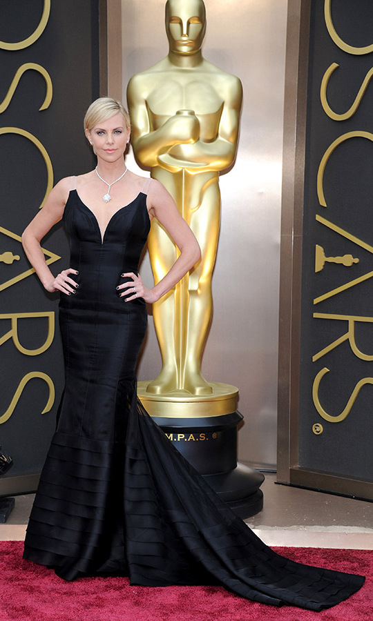 <h2>2014</h2><p>Charlize Theron struck a fierce pose in a statement-making black gown with illusion neckline from <a href=/tags/0/dior><strong>Dior</strong></a> with a <a href=/tags/0/harry-winston><strong>Harry Winston</strong></a> 31-karat diamond pendant.<p>Photo: &copy; Kevin Mazur/WireImage