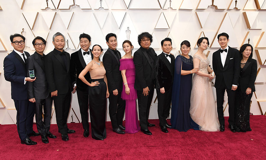The cast and crew of <em>Parasite</em>, including Director <a href=/tags/0/bong-joon-ho><strong>Bong Joon-ho</strong></a> (center), posed together on the 2020 Academy Awards red carpet. <p>Photo: &copy; Jeff Kravitz/FilmMagic