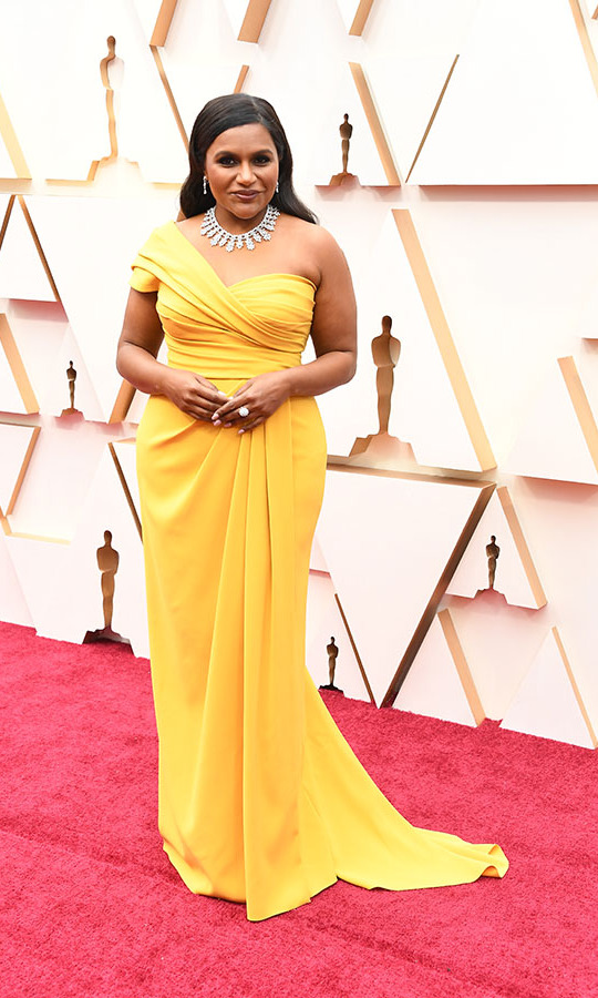 <a href=/tags/0/mindy-kaling><strong>Mindy Kaling</strong></a> shone in a yellow asymmetric <A HREF=/tags/0/dolce-and-gabbana>Dolce & Gabbana</a></strong> gown with dazzling <strong>Chopard</strong> necklace consisting of 8.46 carats of marquise-cut diamonds and 46.33 carats of round-shaped diamonds set in 18-carat white gold. She had Stuart Weitzman shoes on her feet. <p>Photo: &copy; Steve Granitz/WireImage