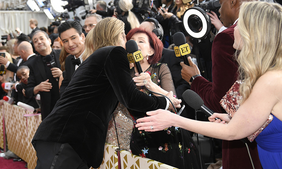 On his way into the show on the red carpet, Brad caught sight of <strong><a href=/tags/0/sharon-osbourne>Sharon Osbourne</a></strong> and gave her a hug. <strong><a href=/tags/0/mario-lopez>Mario Lopez</a></strong> watched on (wishing he also could have a hug?). 