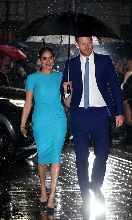 Meghan looked very pleased to be back in the UK, smiling under her husband's umbrella, despite the English downpour. She beamed in a bright turquoise <strong><A href=/tags/0/victoria-beckham>Victoria Beckham</a></strong> dress, which she complemented with a small clutch.