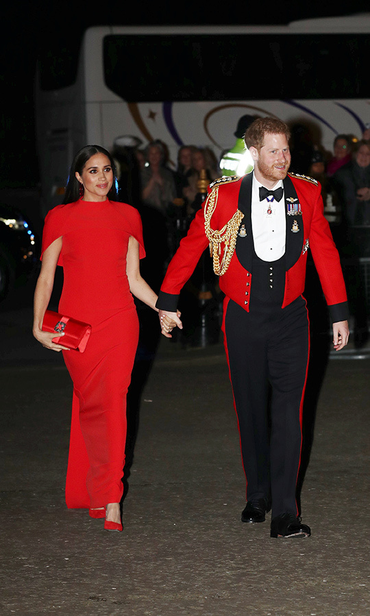 Meghan looked incredible, wearing red from head-to-toe as she and Harry arrived at the event. She chose a red gown from <strong><a href=/tags/0/safiyaa>Safiyaa</strong></a>, which she paired with red <a href=/tags/0/aquazzura><Strong>Aquazzura</strong></a> heels and a red <strong><a href=/tags/0/manolo>Manolo</a></strong> clutch. Harry looked very handsome in his Captain General uniform.