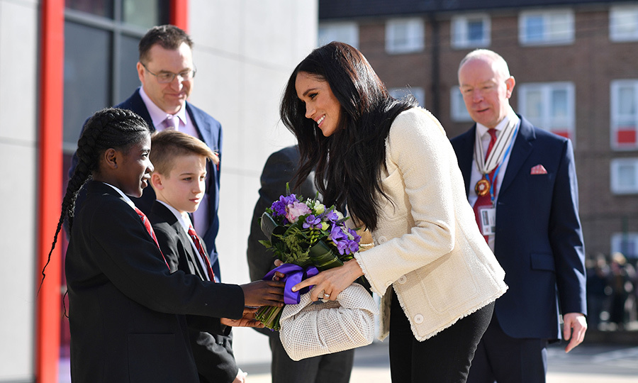 The Duchess of Sussex arrived at the school looking relaxed, happy and thrilled to be there. She was wearing pieces entirely made by women designers, too! 