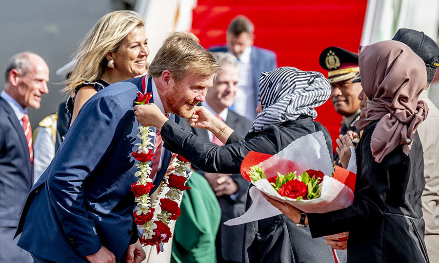 Queen Máxima and King Willem-Alexander are greeted with flowers after their arrival at the airport in Jakarta on March 9.