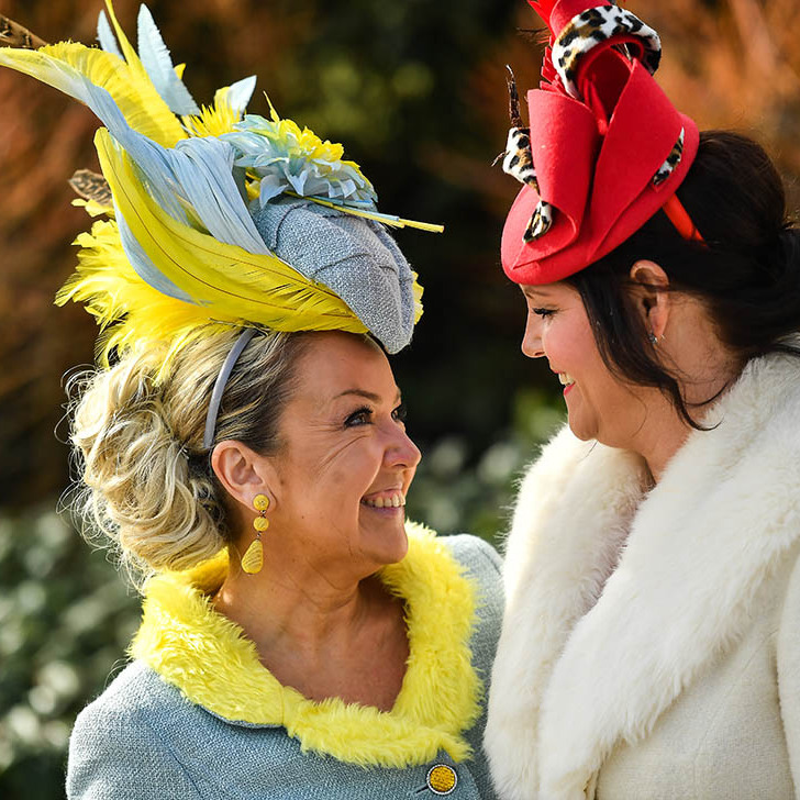 Two racegoers put on their most dramatic, colourful hats for Ladies Day. 