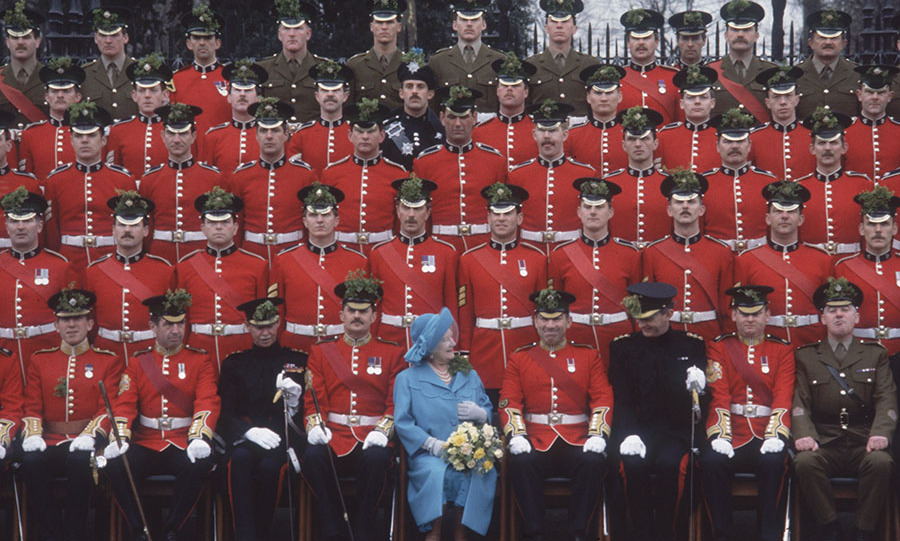 While posing with members of the Irish Guards for a photograph, the Queen Mother shared a joke with them!