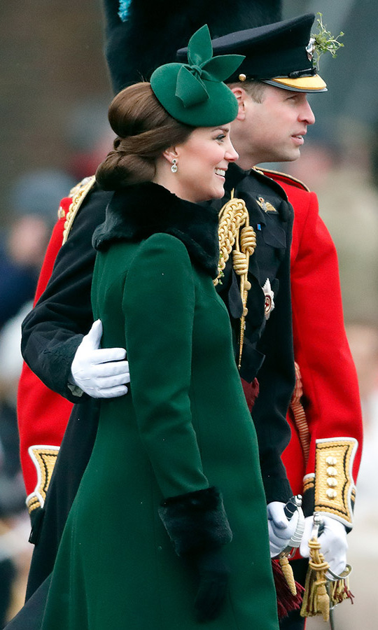 On St. Patrick's Day 2018, the Cambridges shared an affectionate moment when William placed a hand on Kate's back. She was expecting <a href=/tags/0/prince-louis><strong>Prince Louis</strong></a> and showcased her bump in a forest green <a href=/tags/0/catherine-walker><strong>Catherine Walker</strong></a> coat with the bowed <strong>Gina Foster</strong> fascinator she wore to celebrate St. Patrick's Day in 2014.