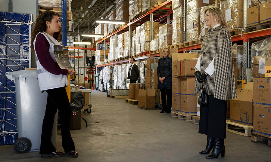 On March 31, <a href=/tags/0/queen-maxima><strong>Queen Máxima</strong></a> spoke with volunteers from the Red Cross in Loenen. She wore a sophisticated layered look consisting of a plaid cape, white blouse, black skirt and square-toed boots.