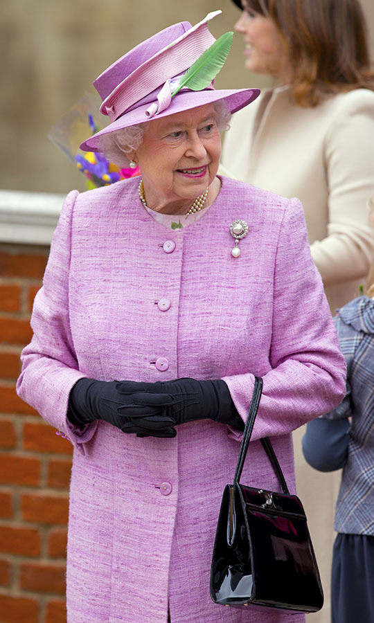 What a pretty shade! Her Majesty wowed in a joyful pink tweed coat and matching hat at Easter Mattins service at Windsor Castle in 2012. The pastel look was accented with a green feather on the brim of her hat!